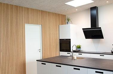 Listevæg i egetræsfiner omkring en dør i et hvidt køkken